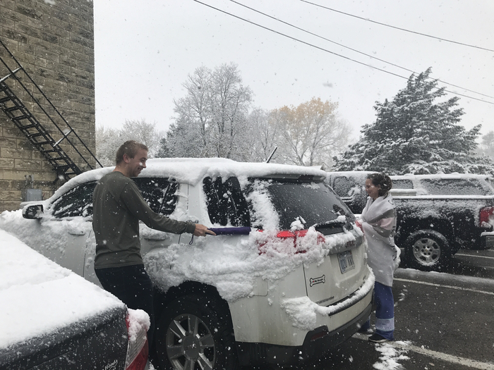 Luke and Shelby showing kindness cleaning off windshields on the teacher's cars!