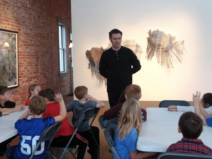 Artist, Caleb Taylor talking with the students.