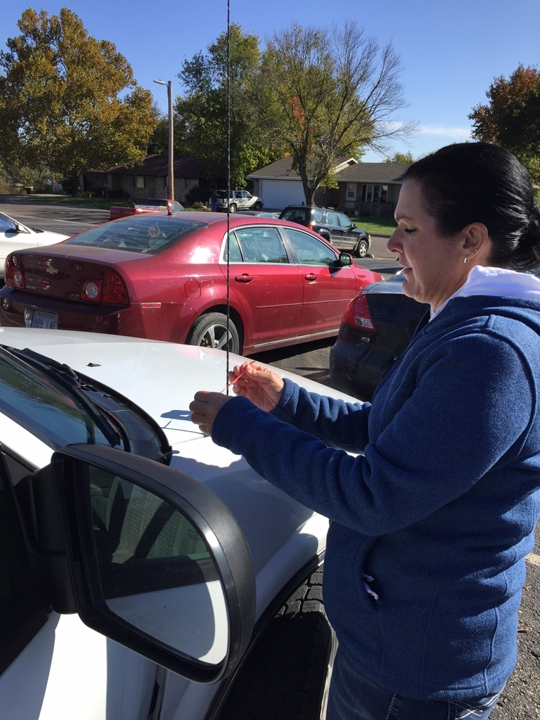 Mrs. Hutley tying red ribbons on students' cars!